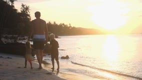 Padre con i bambini che camminano sulla spiaggia Mani del ` s dei bambini della tenuta del papà al bello tramonto Concetto di fes fotografia stock libera da diritti