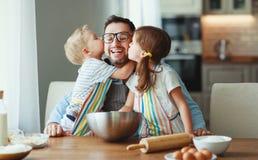 Padre con i bambini che cuociono i biscotti fotografie stock libere da diritti