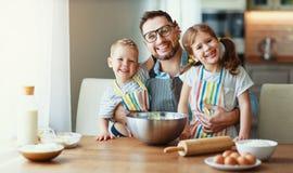 Padre con i bambini che cuociono i biscotti immagine stock libera da diritti