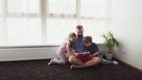 Padre con i bambini che per mezzo di una compressa video d archivio