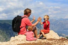 Padre con i bambini di rimorchio divertendosi in montagne Fotografia Stock