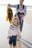 Padre con i bambini sulla spiaggia Immagine Stock