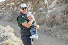 Padre con i suoi 9 mesi di figlio in marsupio sulla traccia immagine stock