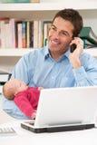 Padre con il bambino appena nato che lavora dalla L usando domestica Fotografie Stock