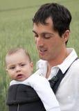 Padre con il bambino in imbracatura Immagine Stock
