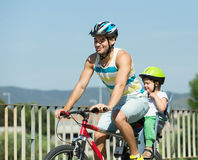 Padre con il bambino sulla bicicletta Fotografia Stock