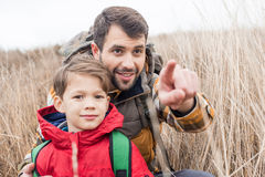 Padre con il figlio che si siede nell'erba Fotografie Stock