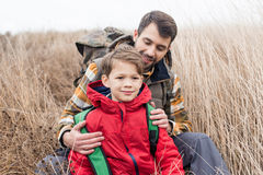 Padre con il figlio che si siede nell'erba Immagini Stock Libere da Diritti