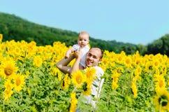 Padre con il figlio sul giacimento del girasole Immagine Stock