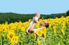 Padre con il figlio sul giacimento del girasole Fotografia Stock Libera da Diritti