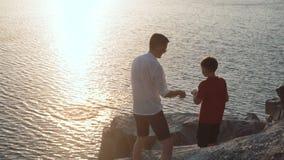 Padre con il figlio sulla riva del lago stock footage