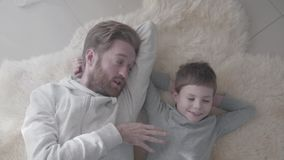 Padre con la barba y su pequeño hijo que miente en la alfombra blanca de la piel y tener conversación interesante Padre-niño metrajes