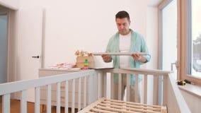 Padre con la cama de bebé de junta de la PC de la tableta en casa almacen de metraje de vídeo