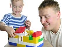 Padre con la casa de la estructura del hijo Foto de archivo libre de regalías