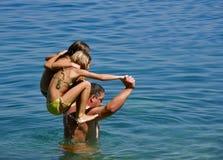 Padre con las hijas en la diversión en el mar Imagenes de archivo