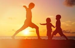 Padre con le siluette dei bambini divertendosi al tramonto fotografia stock