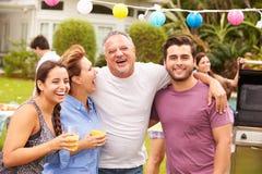 Padre con los niños adultos que disfrutan del partido en jardín Fotografía de archivo