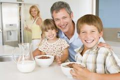 Padre con los niños como comen el desayuno Imágenes de archivo libres de regalías