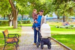 Padre con los niños que caminan en parque de la ciudad Fotos de archivo libres de regalías