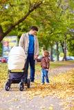 Padre con los niños que caminan en parque de la ciudad Imagen de archivo