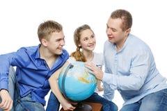Padre con los niños que miran el globo de la tierra Foto de archivo