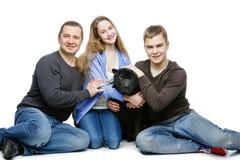 Padre con los niños que sientan el perro Foto de archivo libre de regalías