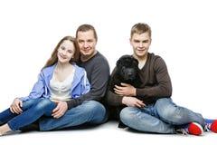 Padre con los niños que sientan el perro Imágenes de archivo libres de regalías