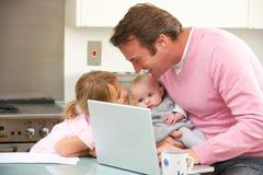 Padre con los niños que usan la computadora portátil en cocina Foto de archivo