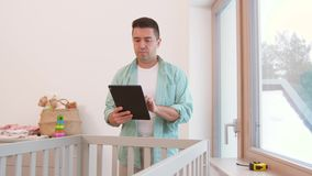 Padre con PC de la tableta y la cama de bebé de medición de la regla almacen de video