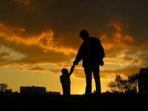 Padre con puesta del sol del bebé Imagen de archivo libre de regalías