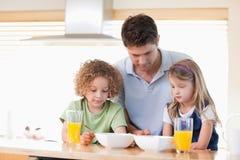 Padre con sus niños que desayunan Imagen de archivo libre de regalías
