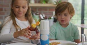 Padre con sus niños que tienen comida en la tabla dinning en casa 4k almacen de video