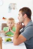 Padre concentrado e hija que ruegan en el almuerzo Imagen de archivo libre de regalías