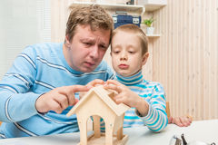 Padre concentrado e hijo que construyen un alimentador del pájaro foto de archivo libre de regalías