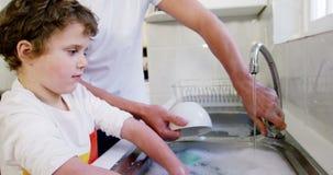 Padre d'aiuto del figlio in utensili di lavaggio archivi video
