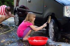 Padre d'aiuto della figlia felice per lavare automobile Fotografia Stock