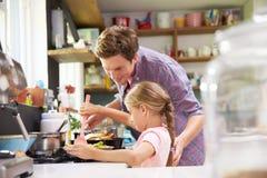 Padre d'aiuto To Cook Meal della figlia in cucina Fotografie Stock