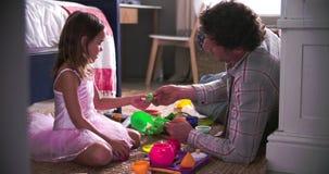 Padre And Daughter Playing con i giocattoli in camera da letto stock footage