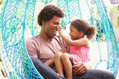 Padre With Daughter Relaxing en el oscilación al aire libre Seat del jardín Fotos de archivo
