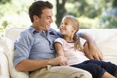 Padre And Daughter Sitting en Sofa At Home Imagen de archivo