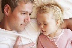 Padre And Daughter Sleeping en cama fotografía de archivo