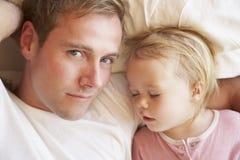 Padre And Daughter Sleeping en cama imagen de archivo libre de regalías