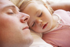 Padre And Daughter Sleeping en cama imagenes de archivo