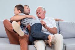 Padre de abarcamiento del hijo en sala de estar Imagenes de archivo