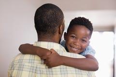 Padre de abarcamiento del muchacho feliz en casa Foto de archivo libre de regalías