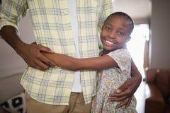Padre de abarcamiento sonriente de la muchacha en casa Fotografía de archivo