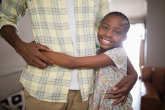 Padre de abarcamiento sonriente de la muchacha en casa Fotos de archivo