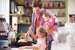Padre de ayuda To Cook Meal de la hija en cocina Imágenes de archivo libres de regalías