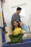Padre de ayuda Washing Clothes de la muchacha Foto de archivo libre de regalías