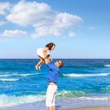 Padre de la familia que detiene a la hija que juega la playa Fotografía de archivo libre de regalías